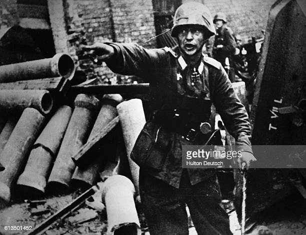 A German officer shouts orders to his men from a barricade in Warsaw Poland during heavy fighting with Polish opponents in September 1944