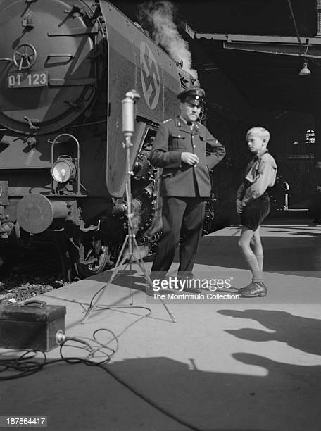 German officer standing on a train station platform alongside a military steam engine with a young boy dressed in Hitler Youth uniform a recording...