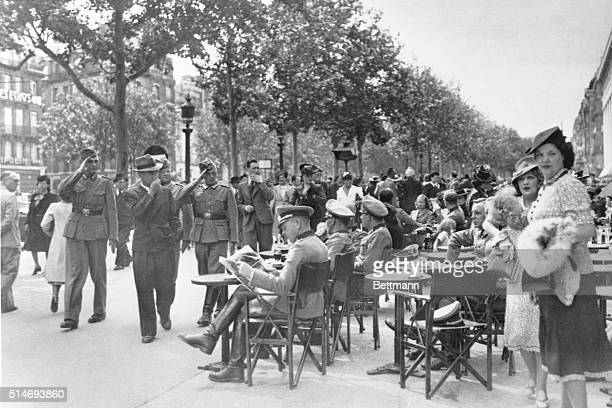 German officers and Parisians mingle near a sidewalk cafe on the Champs Elysees on Bastille Day in 1940. The German armed forces occupied France...