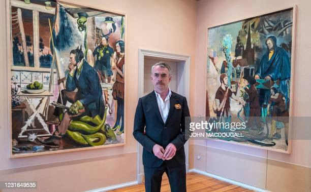 """German painter Neo Rauch poses in front of his paintings """"Die Erwartung"""" and """"Die Wegzehr"""", during a press preview of his exhibition """"Der Beifang"""" at..."""