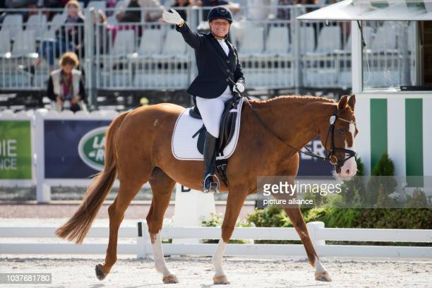 German para dressage rider Hannelore Brenner waves on her horse 'Wonder of the World' during the World Equestrian Games in Caen France 27 August 2014...
