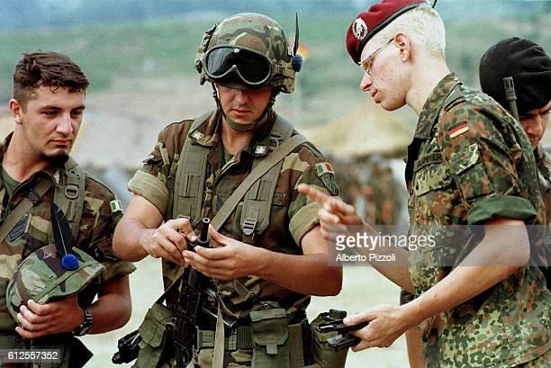 German paratrooper showing a UZI machinepistol to an Italian Alpine troops soldier.