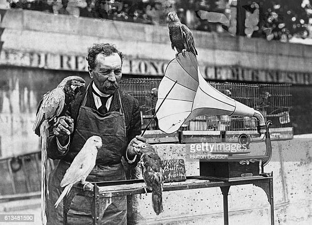 A German parrot seller trains his birds to talk by rote through listening to gramophone records ca 1935