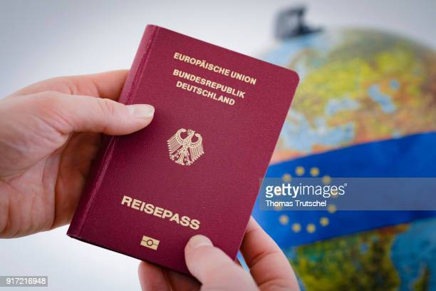 A German passport is held in front of a globe on February 08 2018 in Berlin Germany