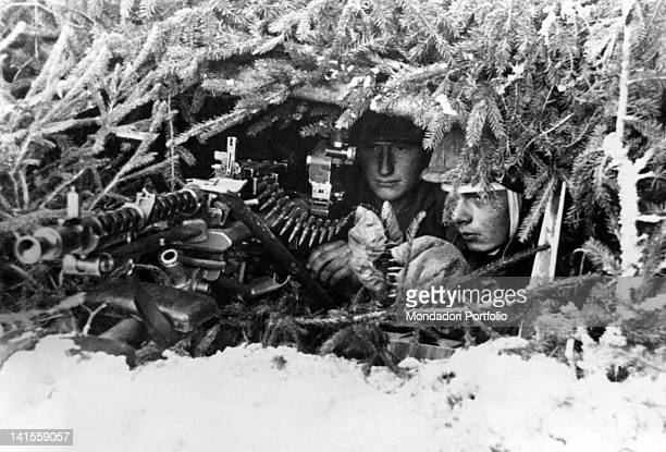A German patrol with machine gun waiting in an advanced camouflaged position on the Russian front east of Leningrad present Saint Petersburg Russia...
