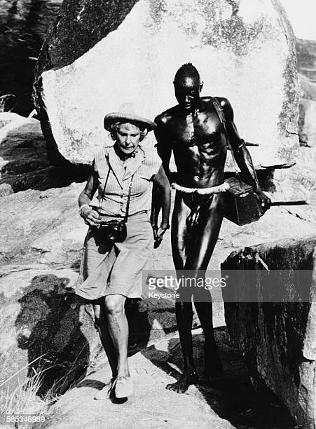German photographer and director Leni Riefenstahl walking with a member of the Nufa tribe, who is carrying her equipment, as she takes photographs...
