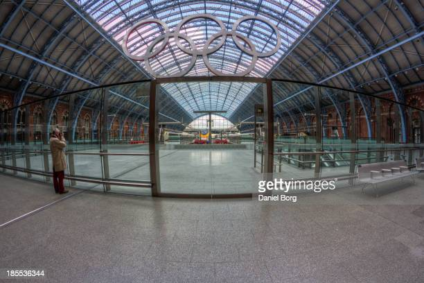 German photographer is seen composing a photo at St Pancras International train station, the Olympic Rings were to mark the celebration of the games...
