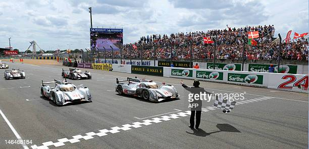 German pilot Andre Lotterer and his Audi R18 ETron Quattro N°1 takes the chequered flag in its 378th and last lap in front of Audi R18 ETron Quattro...