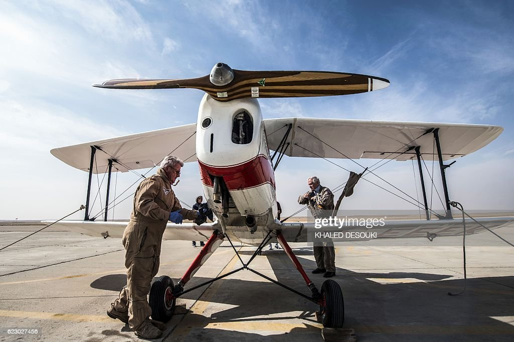 German pilot Ingo Presser (L) checks his Bü 131 Bücker Jungmann biplane after landing at an airfield in Cairo's 6th of October City, west of the Egyptian capital, during the Vintage Air Rally (VAR) on November 13, 2016. A dozen biplanes from the 1920s and 1930s are flying 8,000 miles from Crete to Cape Town in a vintage aviation rally that harks back to the early days of air travel. The pilots will fly along the Nile from Cairo to Khartoum, past the highlands of Ethiopia, down through East Africa past Mount Kilimanjaro, over Victoria Falls, and will end in South Africa. It is the first aviation rally to be granted permission to land at Egypt's Giza pyramids in 50 years, and will put on Sudan's first air show. / AFP / KHALED