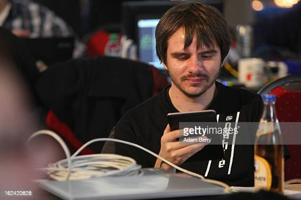 German Pirate Party supporter looks at a tablet computer while sitting next to a bottle of Yerba Mate carbonated tea during a meeting of the Berlin...