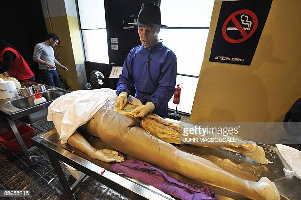 German plastinator Gunther von Hagens dissects a cadaver as he explains the process of plastination on the sidelines of his exhibition Body Worlds...
