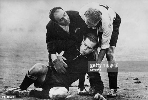 A German player and the referee help injured Germany goalkeeper Fritz Herkenrath during a friendly match at Wembley Stadium London 1st December 1954...