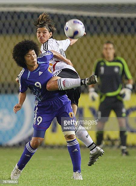 German player Ariane Hingst fights for the ball with Japan player Eriko Arakawa during the 2007 FIFA Women's World Cup soccer tournament Group A...