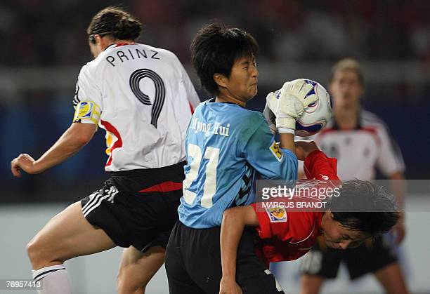German player Birgit Prinz fights for the ball with North Korea goalkeeper Jon Myong Hui during the 2007 FIFA Women's World Cup football match at the...