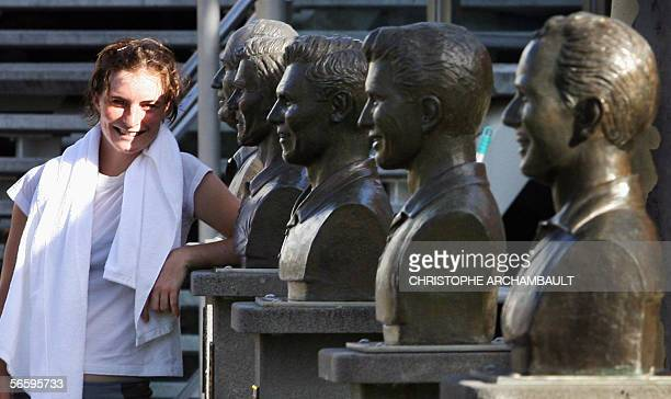 German player Kathrin Woerle poses beside busts of famous Australian tennis players on the eve of the Australian Open tennis tournament in Melbourne...