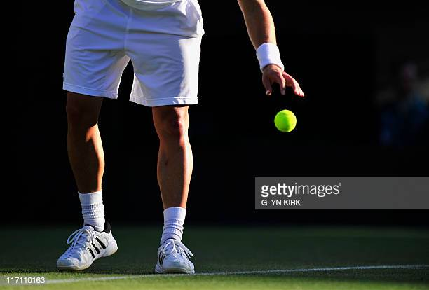 German player Tobias Kamke prepares to serve against British player Andy Murray in a Men's Singles match at the 2011 Wimbledon Tennis Championships...