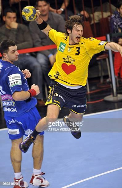 German player Uwe Gensheimer of Rhein Neckar Loewen jumps to score a goal as Hungarian Renato Silic of MKB Veszprem looks on at Veszprem sports hall...