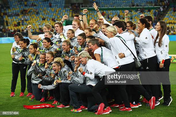 German players celebrate as they receive their medals following victory in the Women's Olympic Gold Medal match between Sweden and Germany at...