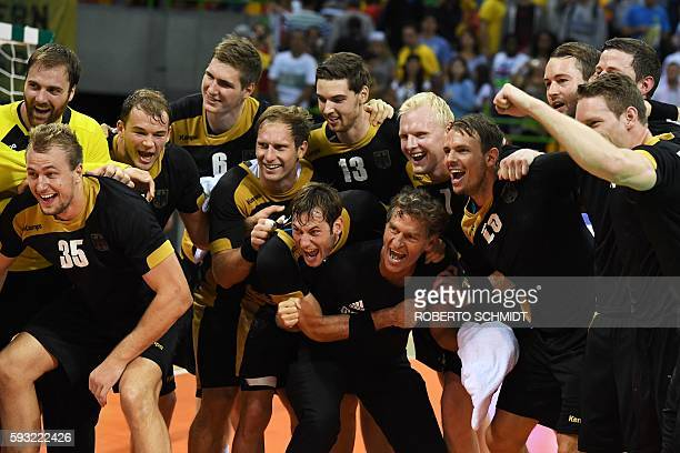 German players celebrate their victory at the end of the men's Bronze Medal handball match Poland vs Germany for the Rio 2016 Olympics Games at the...