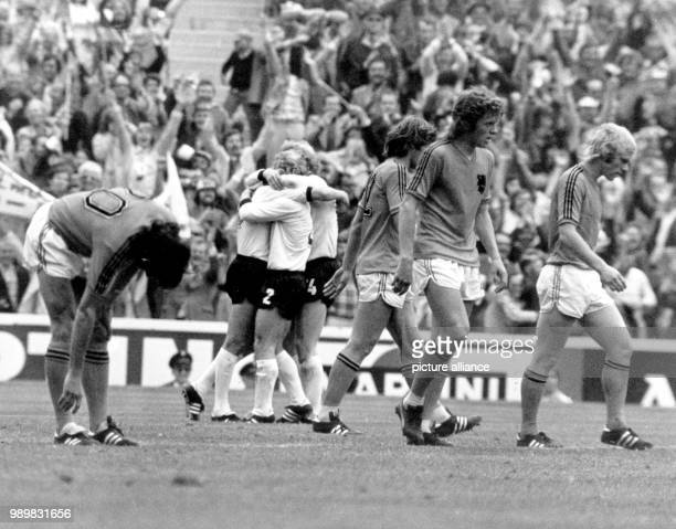 German players Gerd Mueller Berti Vogts and Uli Hoeness form a joyous embrace after Mueller's 21 goahead goal while their Dutch opponents Wim...