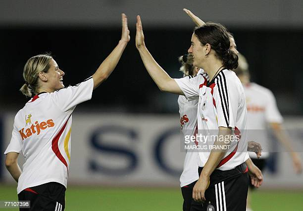 German players Martina Mueller and Birgit Prinz give the high five after a training session in Shanghai 29 September 2007 ahead of the Final Germany...