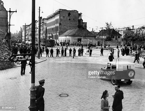 German police and American soldiers face Soviet soldiers at the border between Alliedcontrolled and Sovietcontrolled Berlin in 1948