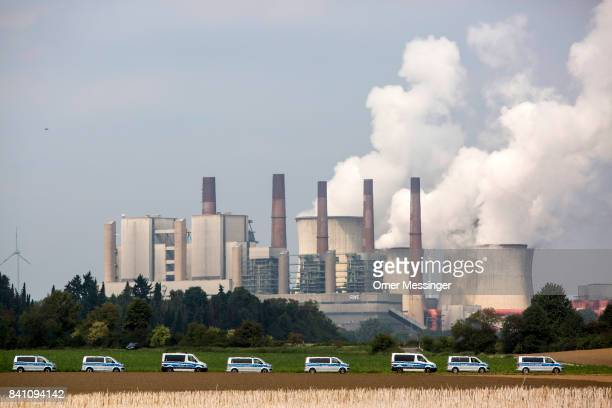 German police cars are parked in a field as the RWE Power AG power plant is seen in the background in the Rhineland mines region west of Cologne on...