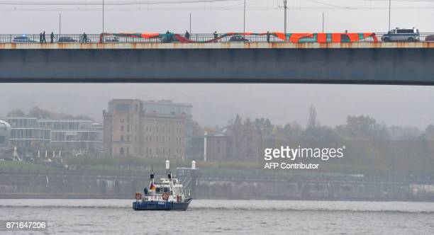 German police disperses anti US president protesters who are about to deploy a giant banner on a bridge over the Rhine river on November 8 2017 in...