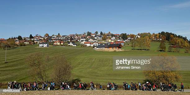 German police lead arriving migrants along a street to a transport facility after gathering them at the border to Austria on October 28 2015 near...