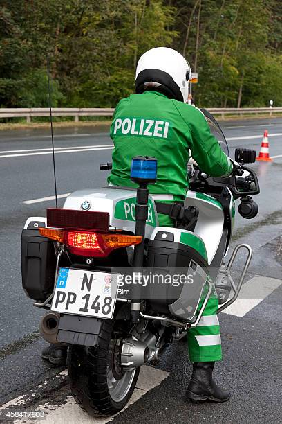 German police motorcyclist standing on side of the road