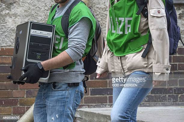 A German police officer carries a seized computer while leaving the association linked to mosque Ibrahim Alkhalil in Berlin's central...