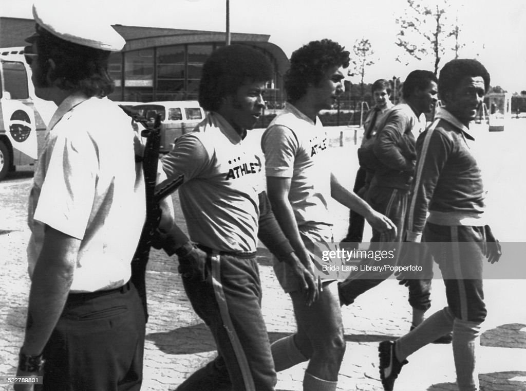 A German police officer (left) keeps watch as Brazilian footballers arrive for a training session at the Niedersachsenstadion, Hanover, during the FIFA World Cup tournament, Germany, 24th June 1974. Left to right: Jairzinho, Nelinho, Luís Pereira and Paulo Cézar.