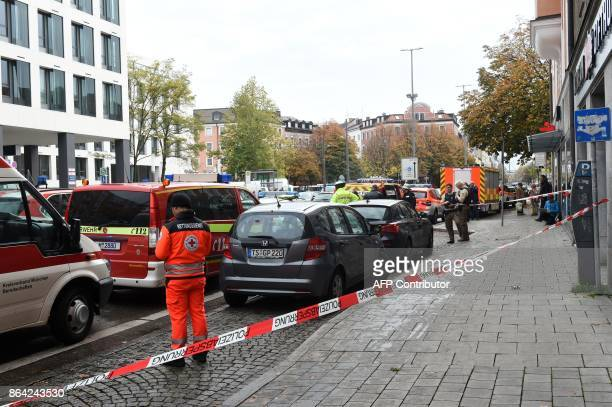 German police officers and emergency personnel stand inside a security perimeter that was set after a man attacked passersby near Rosenheimer square...