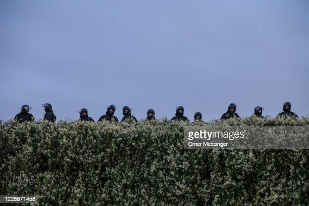 German police officers observe behined a hedge as supporters of the far-right Third Way neo-Nazi political party gathering on the 30th anniversary of...