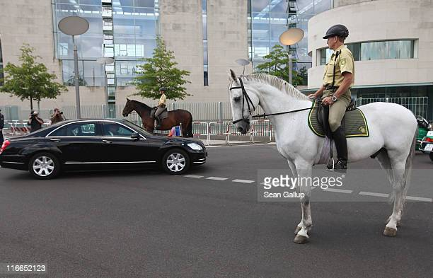 German police on horses watch as French President Nicolas Sarkozy arrives for talks with German Chancellor Angela Merkel at the Chancellery on June...