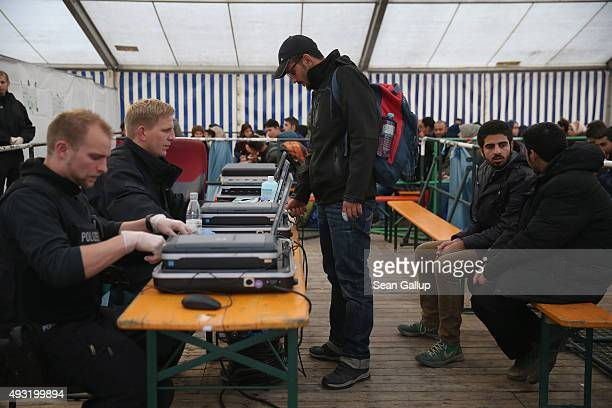 German police scan the finger print of an arriving migrant to determine whether he already exists in any European register at a reception tent for...