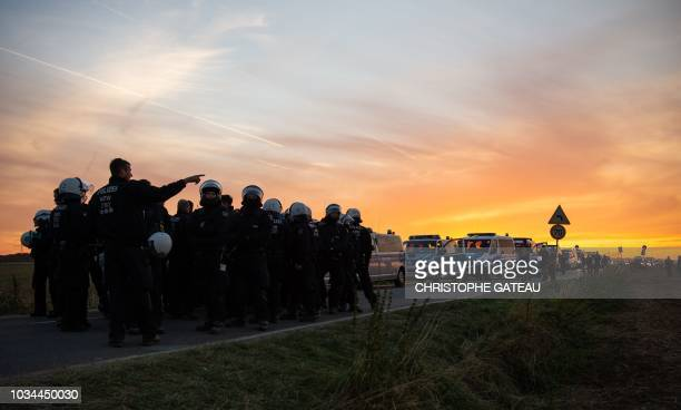 TOPSHOT German police stand next to their vehicles after a demonstration against the deforestation of parts of the Hambacher Forest by German energy...