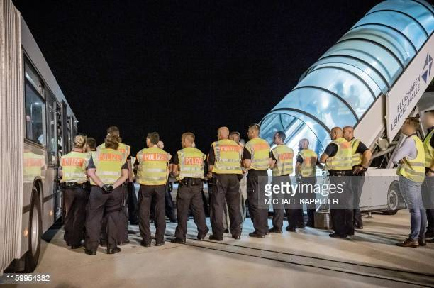 German police stands guard as police officers escort a rejected Afghan asylum seeker to board an aircraft heading to Kabul, on August 1, 2019 at an...
