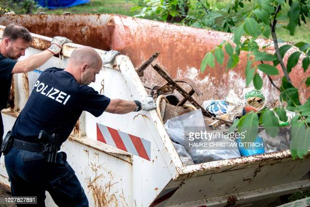 German police work next to a skip during a search in a garden allotment in the northern German city of Hanover on July 29 in connection with the...