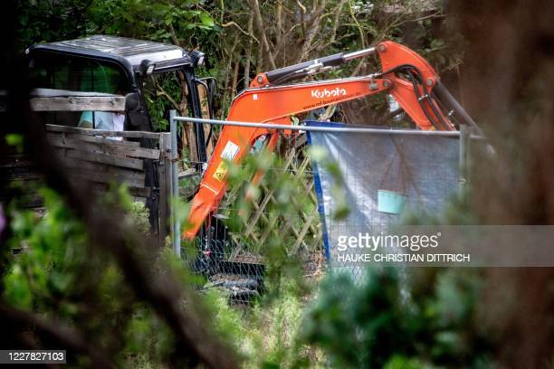 German police work with a digger during a search in a garden allotment in the northern German city of Hanover on July 29 in connection with the...