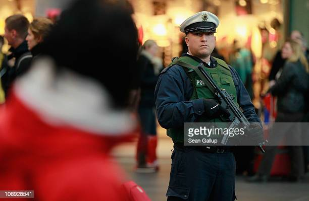 German policeman armed with a submachine gun keeps a watchful eye among travelers at Hauptbahnhof main railway station on November 17 2010 in Berlin...