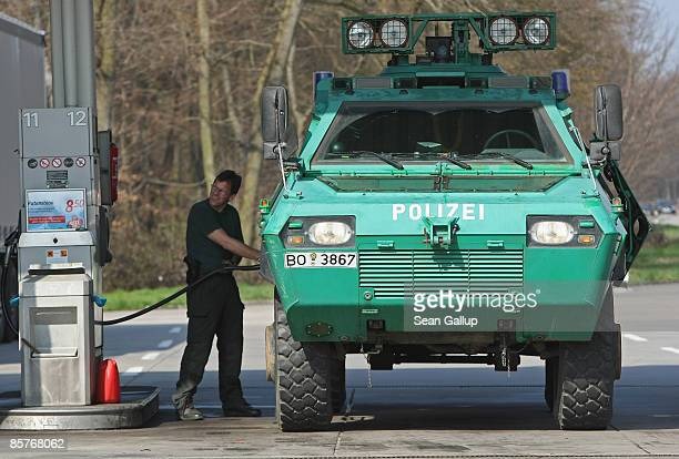 German policeman fills a police armoured car with gasoline at a highway gas station on his way to the upcoming NATO summit in BadenBaden and...