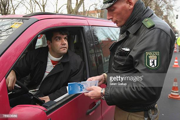 German policeman hands out a flyer with information about Berlin's environment zone to a driver who does not yet have an environment zone sticker on...