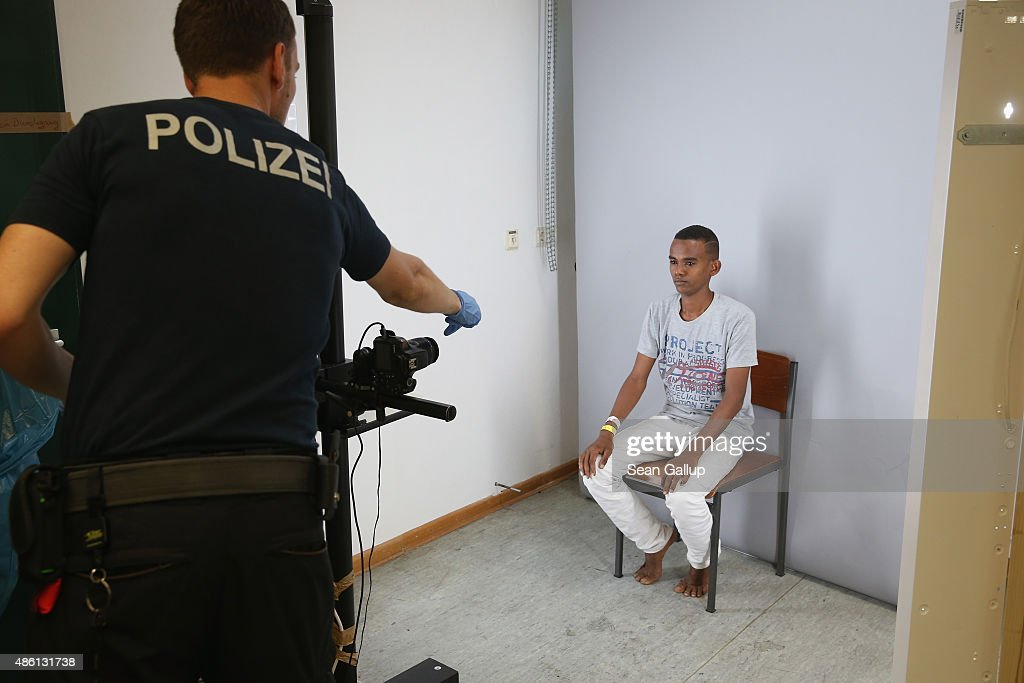 A German policeman prepares to photograph a newly-arrived migrant from Eritrea as part of the registration process at a center for migrants at a facility of the German Federal Police (Bundespolizei) on August 31, 2015 in Rosenheim, Germany. German police monitor trains arriving from the Balkans and from Italy that go through Rosenheim and currently detain around 350 people a day for travelling without a passport. The police register the migrants, mostly from countries including Syria, Afghanistan and Eritrea, fingerprint them and check whether any are already in the European asylum-applicants or criminal databases. From there the migrants are free to travel within Germany to reception centers where they can apply for asylum. Up to 1,600 migrants are currently arriving in Bavaria in southern Germany a day and will seek asylum. Germany is expecting to receive 800,000 asylum-seeking migrants this year and is struggling to cope with the record number.