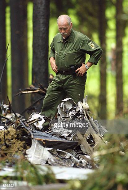 German policeman stands over the wreckage of a DHL Boeing 757 cargo plane July 2, 2002 in a forest near the town of Taisersdorf, Germany. The...