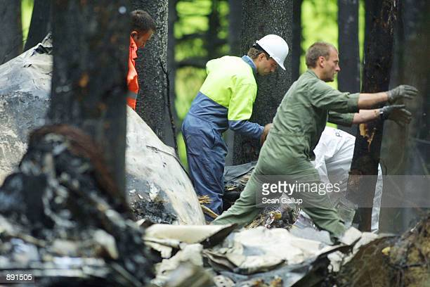 German policemen and firefighters sort through the charred wreckage of a DHL Boeing 757 cargo plane July 2, 2002 in a forest near the town of...