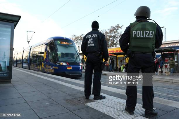 German policemen wait for the arrival of a tramway to control commuters in Kehl, on December 13 as part of the hunt for the gunman who killed three...