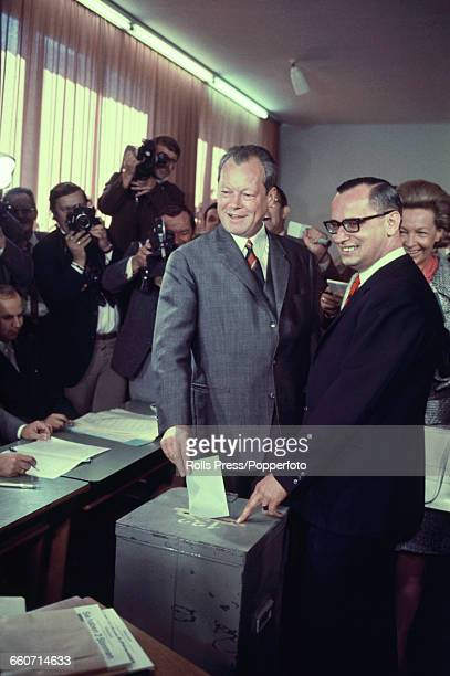 German politician and leader of the Social Democratic Party Willy Brandt pictured in centre placing his vote slip in the ballot box in front of news...