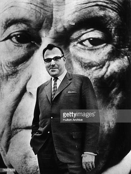 German politician Helmut Kohl posing with a large photograph of the late chancellor Konrad Adenauer after being reelected to the national chair of...