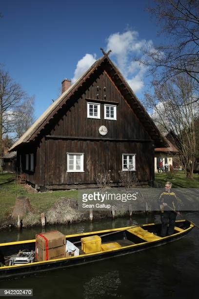 German postal carrier Deutsche Post postal worker Andrea Bunar guides her flat-bottomed canoe past a house as she delivers the mail in the web of...